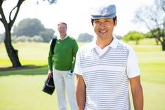 Amis jouants au golf souriant à l'appareil-photo Photographie stock