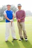 Amis jouants au golf souriant à l'appareil-photo tenant des clubs Photo libre de droits