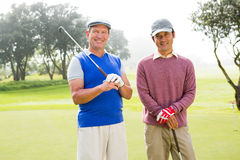 Amis jouants au golf souriant à l'appareil-photo tenant des clubs Photos libres de droits
