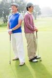 Amis jouants au golf souriant et tenant des clubs Photographie stock libre de droits