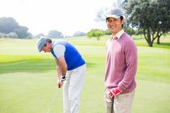Amis jouants au golf sur le putting green Images libres de droits