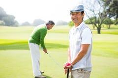 Amis jouants au golf sur le putting green Image libre de droits