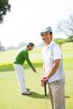 Amis jouants au golf sur le putting green Image stock