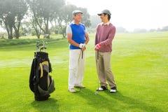 Amis jouants au golf tenant des clubs Photo stock
