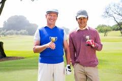 Amis jouants au golf tenant des tasses souriant à l'appareil-photo Image stock