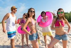 Amis joyeux ayant l'amusement sur la plage Photo stock