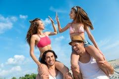 Amis joyeux ayant l'amusement sur la plage Image libre de droits