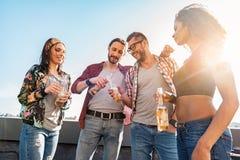 Amis joyeux buvant l'alcool sur la terrasse de dessus de toit Photos stock