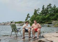 Amis joyeux drôles parlant la détente riante en parc près du lac Image libre de droits