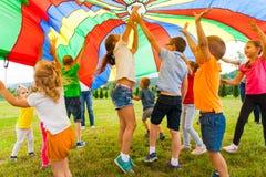 Amis joyeux essayant d'attraper le parachute de vol Images libres de droits