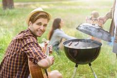 Amis joyeux faisant le pique-nique dans la forêt Images stock