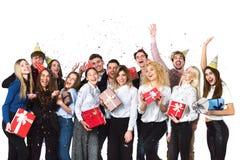 Amis joyeux gais des jeunes se tenant et célébrant ensemble au-dessus du fond blanc Images libres de droits