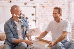 Amis joyeux jouant dans un jeu de puzzle à la maison Photographie stock