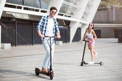 Amis joyeux montant des scooters de coup-de-pied Photos stock
