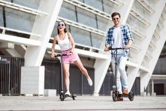 Amis joyeux montant un scooter de coup-de-pied Photographie stock libre de droits