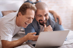 Amis joyeux observant des vidéos à la maison Photos libres de droits