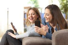 Amis joyeux partageant le contenu futé de téléphone à la maison photographie stock libre de droits