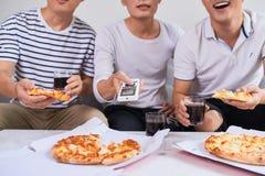 Amis joyeux positifs appréciant leur pizza Photographie stock libre de droits