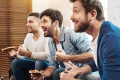 Amis joyeux positifs appréciant leur pizza Photos libres de droits