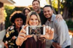 Amis joyeux prenant le selfie pendant la partie extérieure Image libre de droits