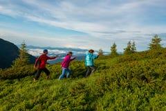 Amis joyeux, voyageurs ayant l'amusement en montagnes Photos stock
