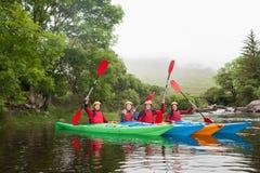 Amis kayaking ensemble encourageant à l'appareil-photo Photographie stock libre de droits