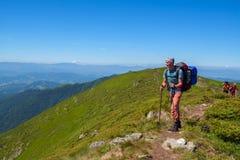 Amis - les hommes et le garçon avec des sacs à dos vont sur une traînée de montagne Images libres de droits