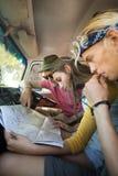 Amis lisant la carte dans le camping-car Photographie stock