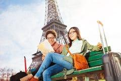 Amis lisant la carte de Paris se reposant sur le banc Photographie stock libre de droits
