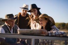Amis lisant la carte pendant des vacances de safari Image libre de droits