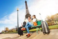 Amis lisant la carte se reposant près de Tour Eiffel Image libre de droits