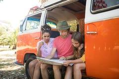 Amis lisant la carte tout en se reposant dans le camping-car Photographie stock