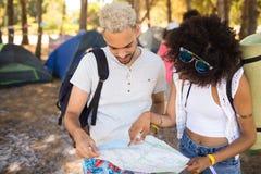 Amis lisant la carte tout en se tenant sur le champ Photographie stock libre de droits