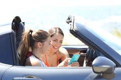 Amis lisant le contenu de téléphone à l'intérieur d'une voiture des vacances Photos stock