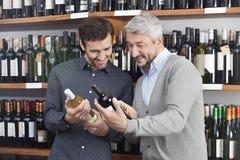 Amis lisant le label des bouteilles de vin dans la boutique Photo libre de droits