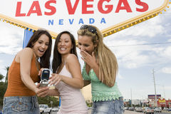 Amis lisant le message sur le téléphone portable et rire Photographie stock