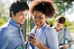 Amis lisant le message textuel sur le téléphone portable dedans Images stock