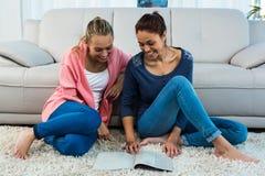 Amis lisant sur le tapis Photos stock