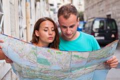 Amis loking sur la carte sur la rue Ils ont lieu en vacances Photo stock