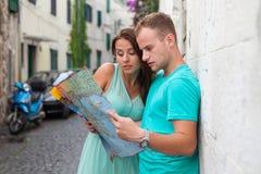 Amis loking sur la carte sur la rue Ils ont lieu en vacances Image libre de droits