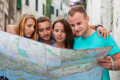 Amis loking sur la carte sur la rue Ils ont lieu en vacances Images stock