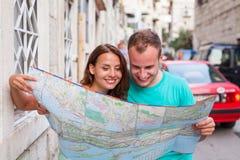 Amis loking sur la carte sur la rue Ils ont lieu en vacances Image stock