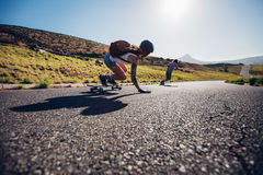 Amis longboarding en bas de la route Photos stock