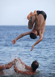 Amis mâles jouant en mer Photo libre de droits