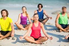 Amis méditant en position de lotus sur le rivage Photographie stock libre de droits