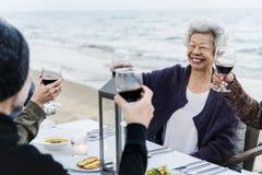 Amis mûrs buvant du vin à la plage Photographie stock