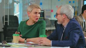 Amis mûrs discutant le projet dans le bureau de démarrage pendant la pause clips vidéos