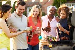 Amis mûrs appréciant le barbecue extérieur d'été dans le jardin Photo stock