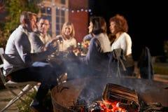 Amis mûrs appréciant le dîner extérieur autour de Firepit Image libre de droits