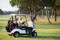 Amis mûrs de golfeur s'asseyant dans le boguet de golf Image libre de droits